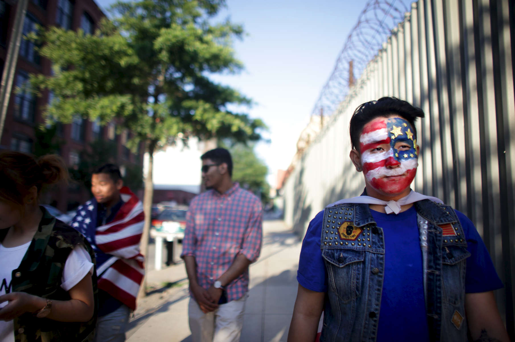 (L-R) Tenzin Dolkar, Tenzin Norsang, Hussein Khalique, and Tenzin Norgay walk around DUMBO during halftime of a screening of the US-Portugal World Cup game under the Manhattan Bridge archway in Brooklyn on June 22, 2014. The game ended 2-2 in overtime. (For The New York Times)