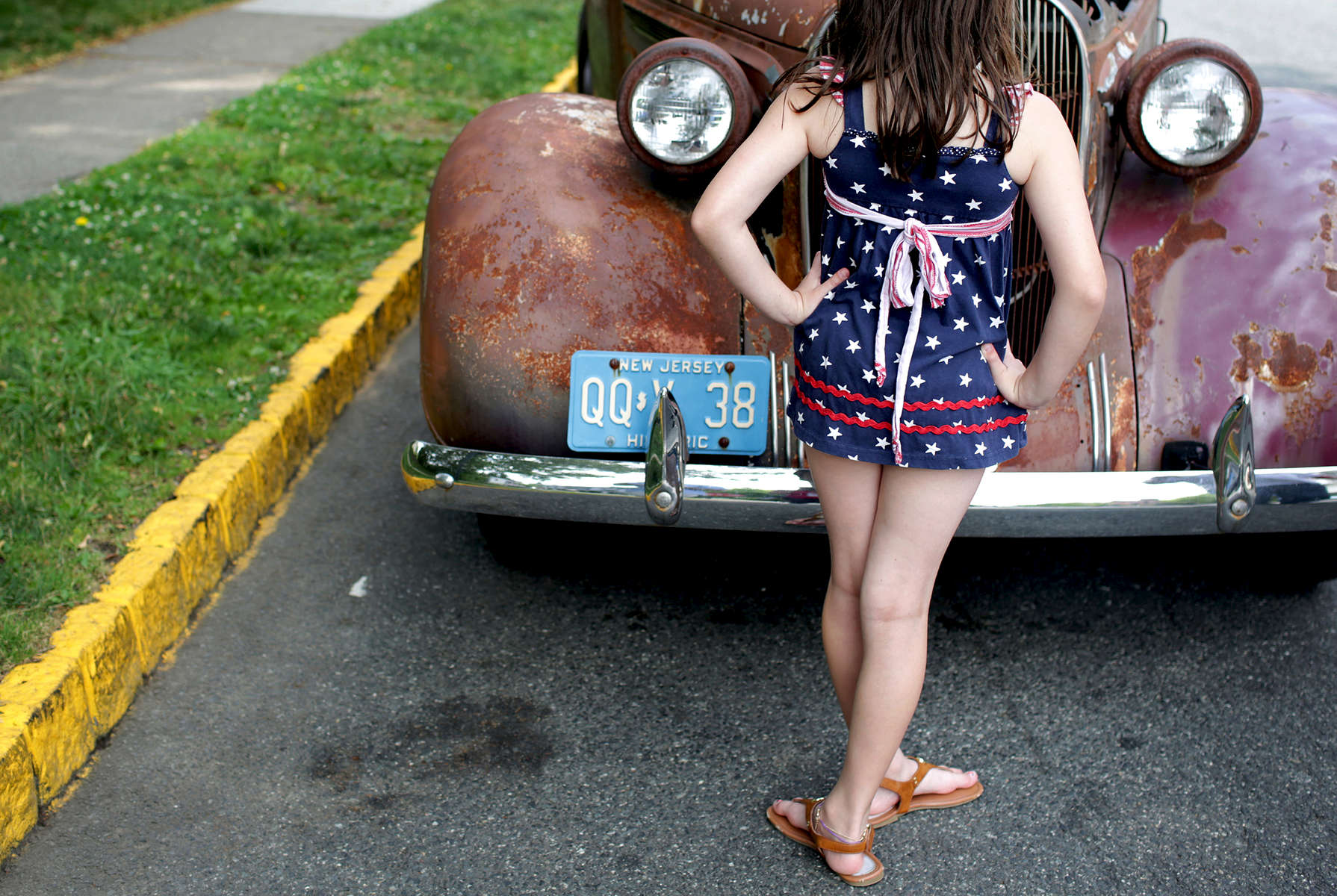 Felicita Pomares, 9, checks out a 1938 Plymouth Road King vintage car, on the way to the Fourth of July Parade in Montclair, NJ, on July 04, 2017.(For The New York Times)