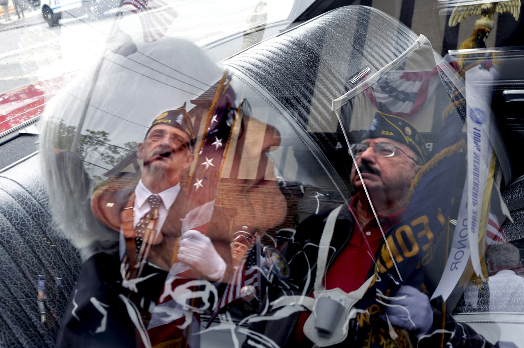 Veterans' reflections are seen on the car window of Eve Stollak, wife of army veteran Jack Stollack, as they prepare to participate in the The Little Neck-Douglaston Memorial Day Parade, the largest in the nation, in Little Neck, NY on May 29, 2017.(For The New York Times)