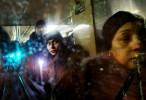 Aude Back de Surany, center, and other passengers are reflected in the back window of an uptown C train traveling through a subway tunnel in New York, New York on January 30, 2015. (For The New York Times)