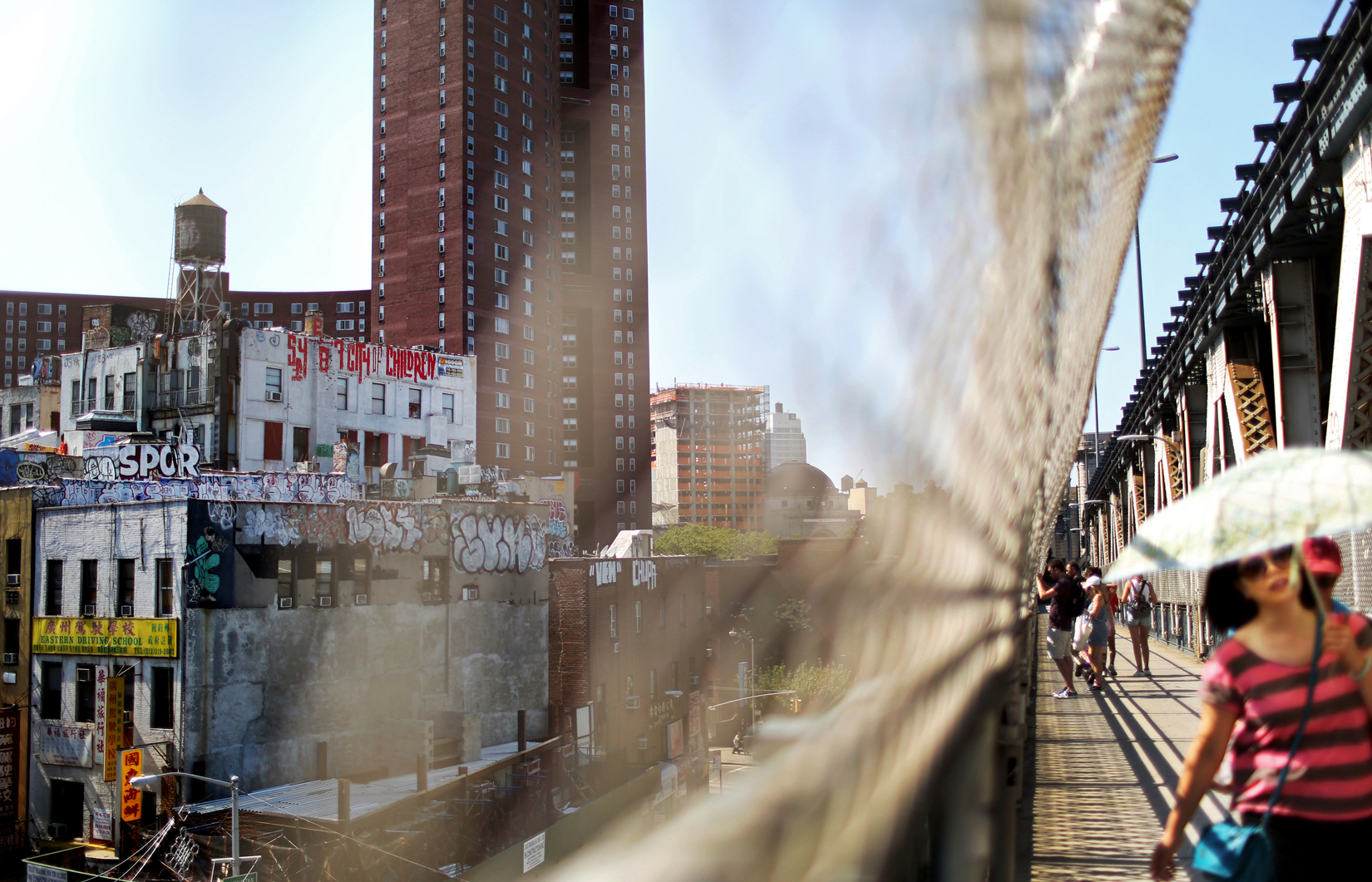A pedestrian shields herself from the afternoon sun walking across the Manhattan bridge toward Brooklyn, with the graffitied buildings of Chinatown in the background, in New York, New York, on July 16, 2015. (For The New York Times)(For The New York Times)