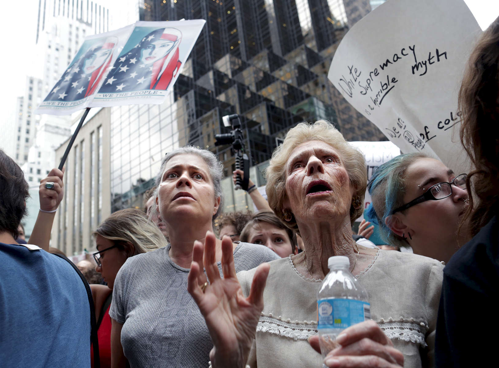 "(L-R) Hillary Ewing and her aunt, Sally Weiner, join thousands of people in front of Trump Tower in Manhattan, NY, on August 14, 2017, protesting this weekend's violent white nationalist rallies in Charlottesville, Virginia.-""Trump Gawkers{quote} is a visceral look at what draws people to Trump Tower, the current residence of U.S. President elect Donald Trump. Hoards of people undertake the trek, bearing security and weather roadblocks, to stare, gawk, absorb, record. The magnetism to the tower (and by extension, to the man inside it,) manifests in the sheer numbers of daily visitors, as well as in the fascination etched across their faces. Upon first look, the time so many spend there seems like sport and amusement, but underneath upturned eyes and selfie smiles prevails an undercurrent of anxiety - and not just for those who didn't want Trump in the Oval Office. Some of the electorate that voted against Hillary is now unsure for which version of Trump they voted. People's upward gazes, no matter their political views, seek answers: How could this happen? Or now that it has, what will it mean?"