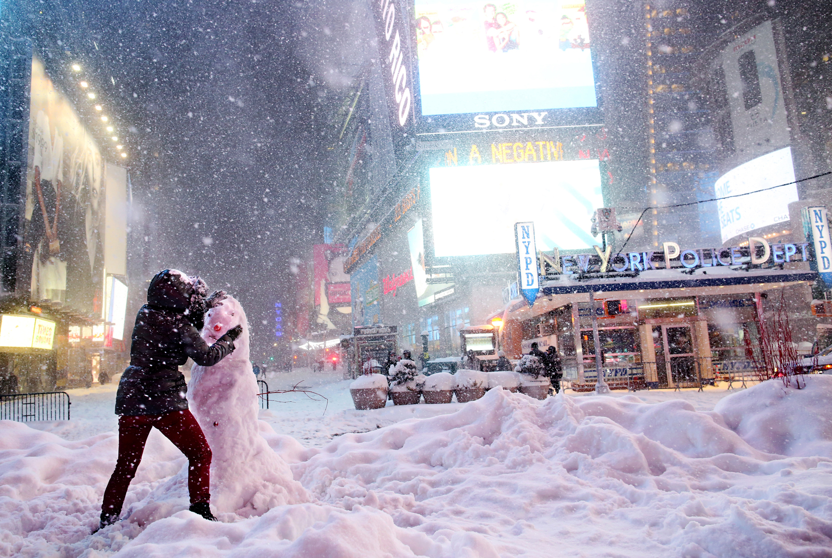 A woman decorates a snowman in Times Square as all cars but emergency vehicles are banned from driving on the roads on January 23, 2016 in New York, NY. The Northeast and parts of the South experienced heavy snow and ice from a slow-moving winter storm, resulting in numerous traffic collision deaths.