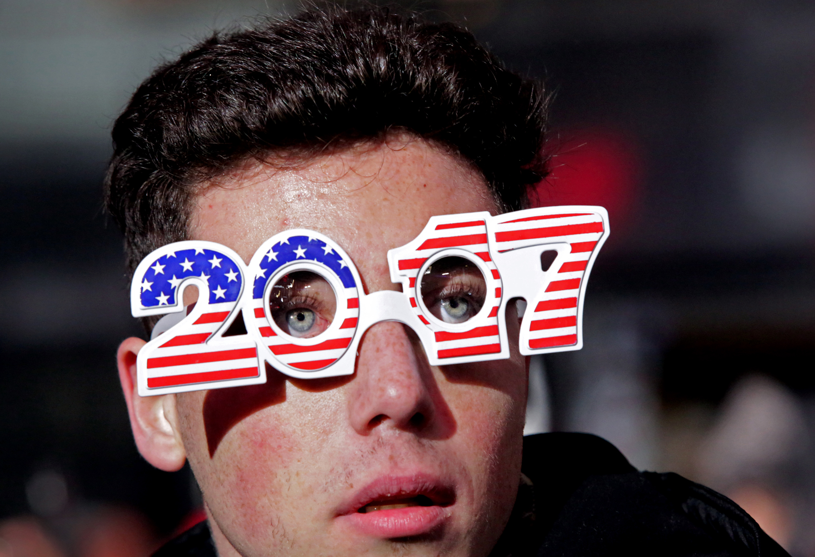 A man peers out from his glasses as people congregate in the lead-up to New Year's eve celebrations in Times Square in New York, NY on December 31, 2016.