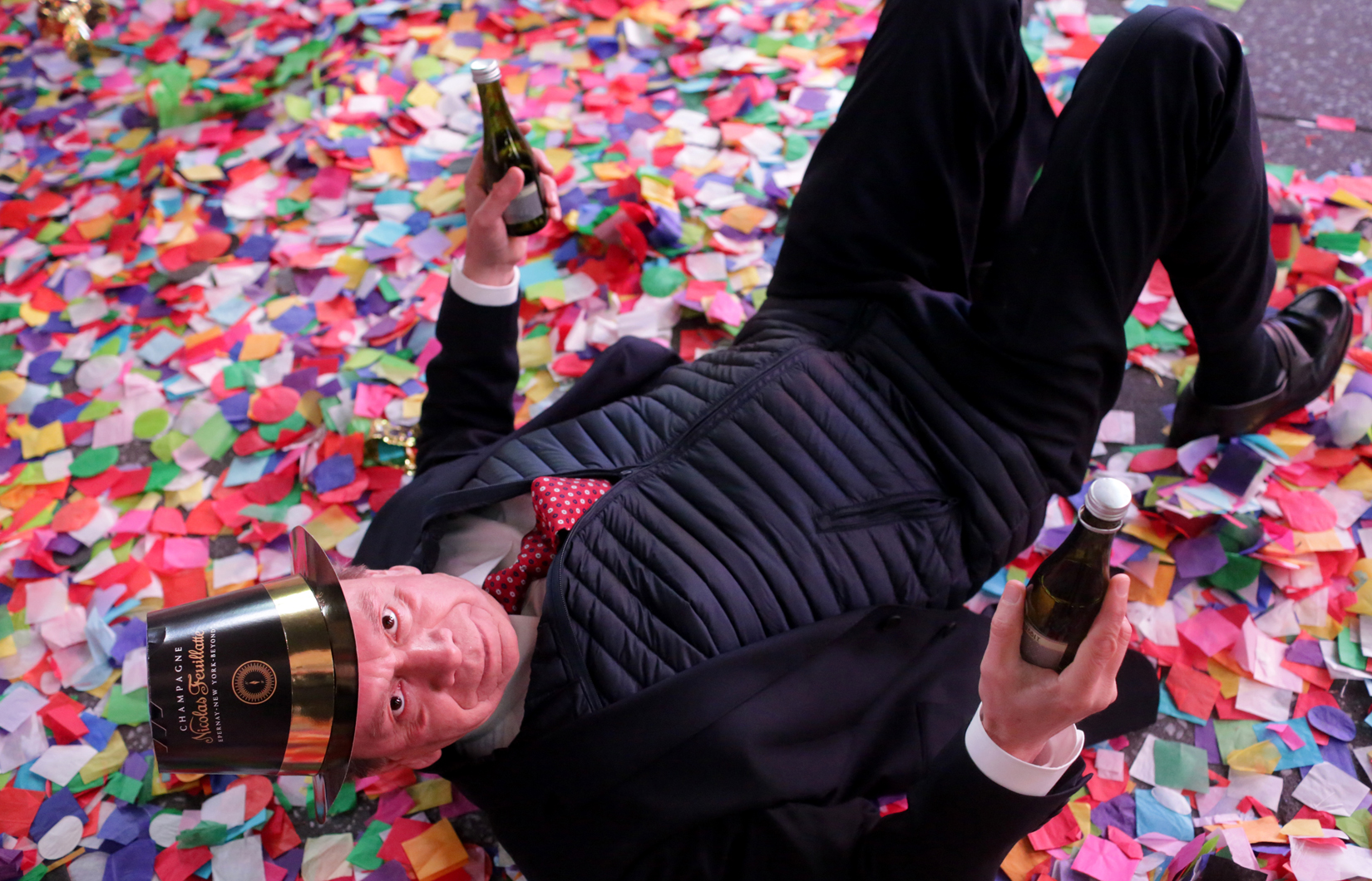 A man rolls around in confetti on New Year's eve in Times Square in New York, NY just after midnight on January 01, 2017.