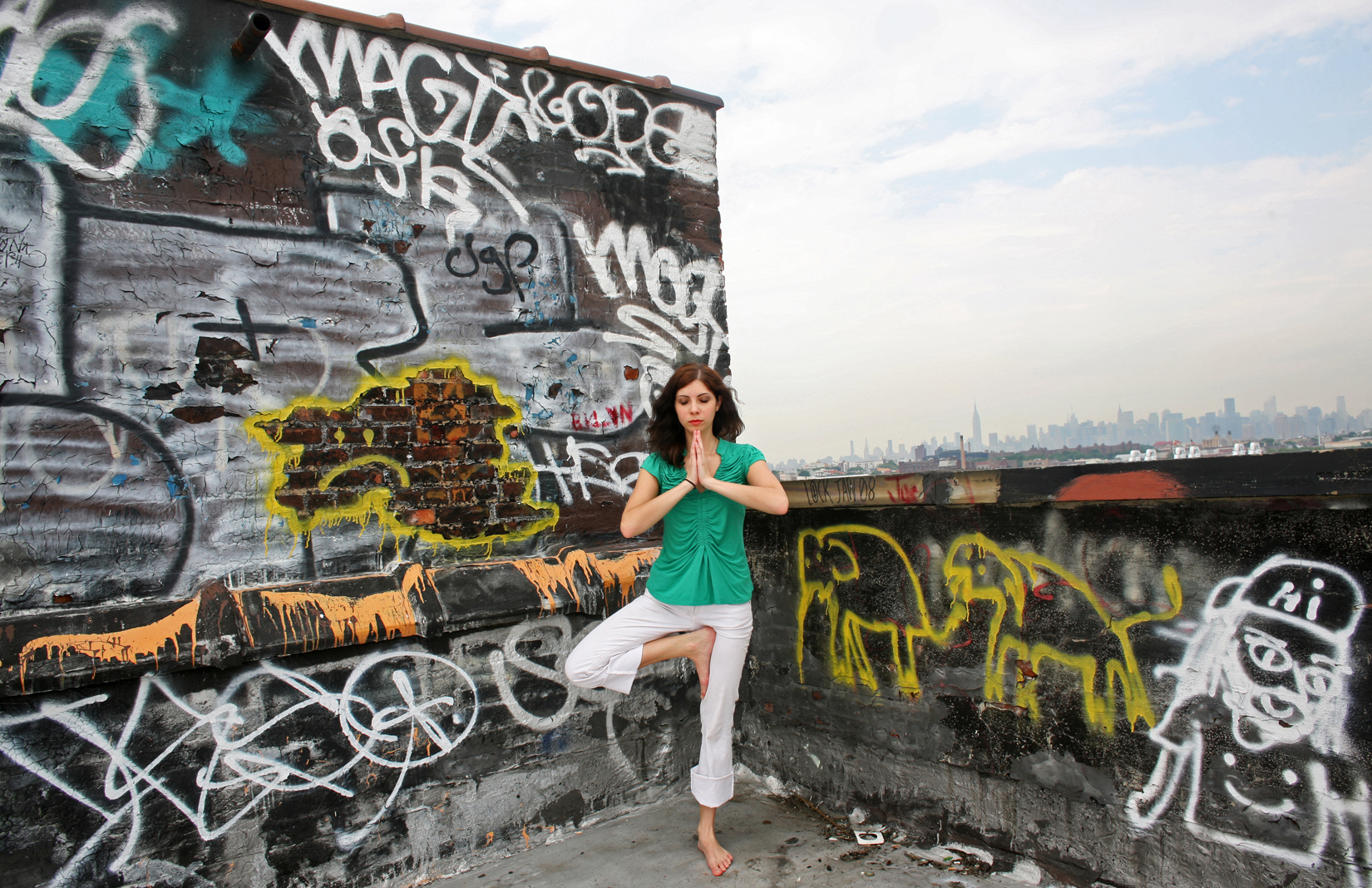 Erin Laubenheimer, in a yoga pose on the rooftop of her apartment building in the Bushwick neighborhood of Brooklyn, NY, on June 26, 2009.  Laubenheimer is an artist looking for work, who does yoga in her spare time to reduce stress. (For The New York Times)