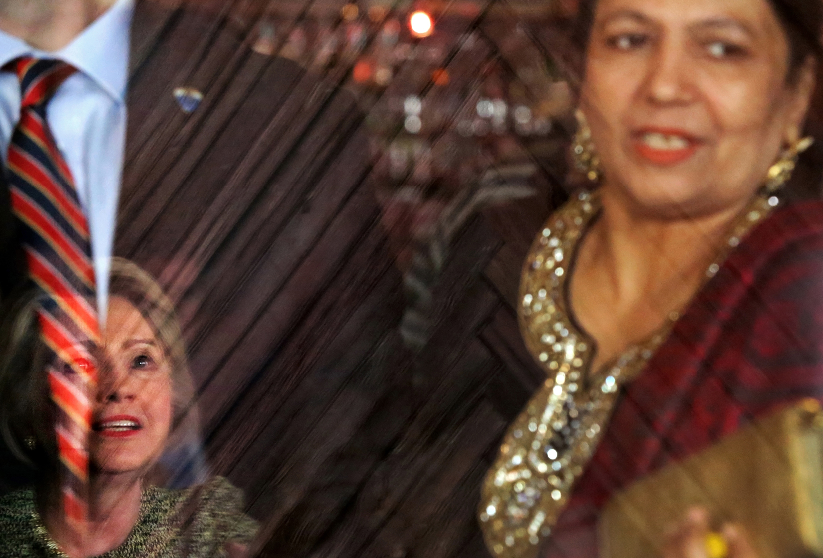 U.S. Presidential candidate Hillary Clinton (D-NY),) on left, speaks at Jackson Diner in Queens, NY, on April 11, 2016. Clinton is seen in the restaurant door's reflection.