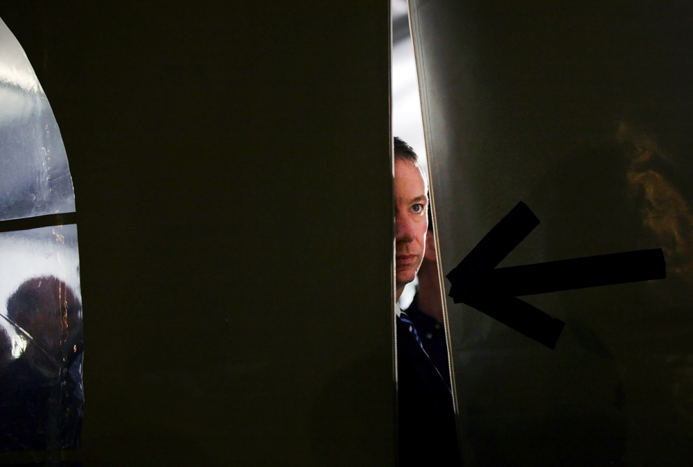 A member of the Secret Service peeks the the outside world from the tent where Republican Presidential candidate Mitt Romney (R-MA) spoke near the Montgomery Inn Restaurant at The Boathouse in Cincinnati, Ohio on Saturday, March 03, 2012.