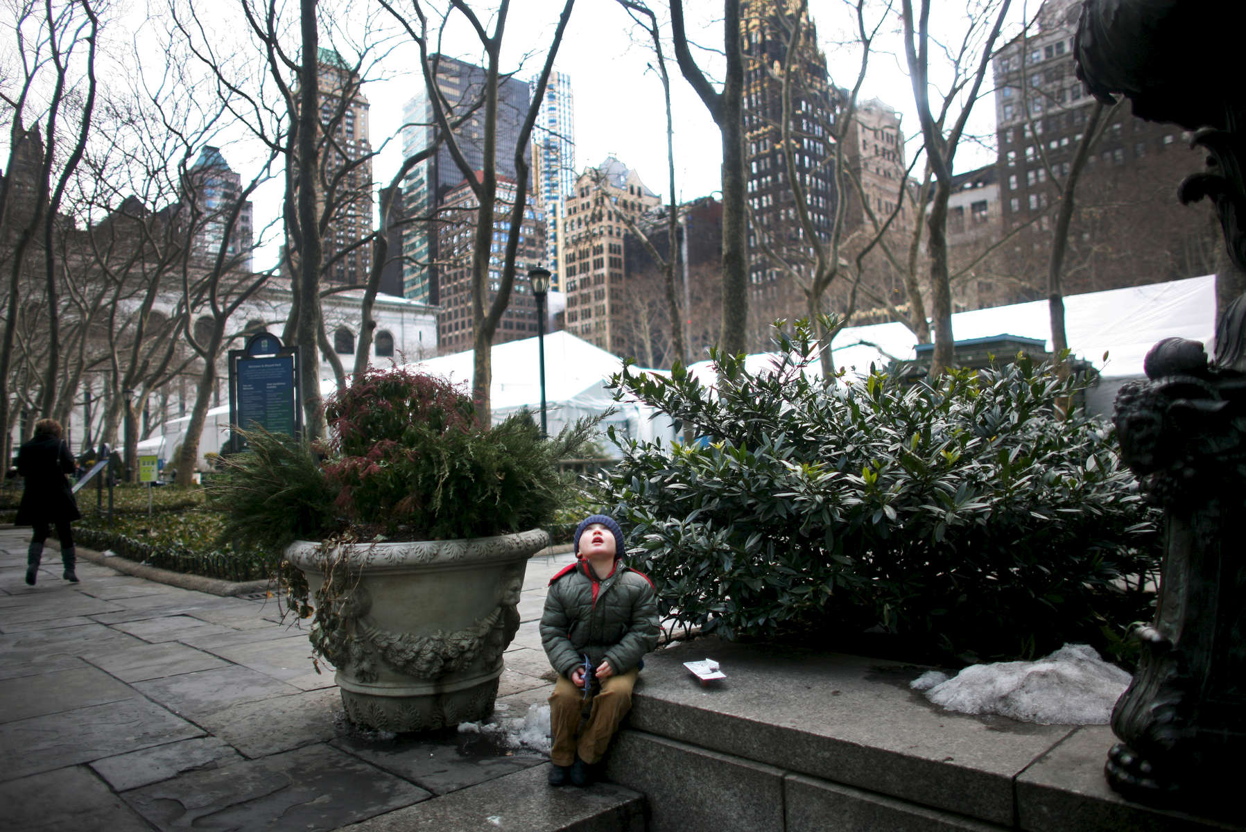 A little boy stares at the trees above Bryant Park on Thursday, February 18, 2010, the last day of Fall 2010 Fashion Week in Manhattan, New York. (For The New York Times)