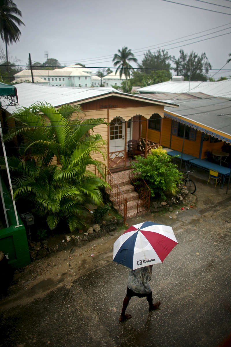 A man shields himself from the rain in Holetown in Barbados on Saturday, April 10, 2010. (For The New York Times)