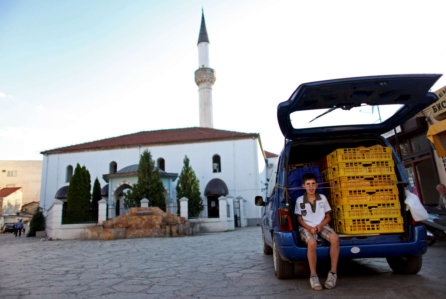 A boy plays with strings holding crates inside a car near the Murat Pasha mosque in the Old City portion of Skopje, Macedonia on Sunday, September 05, 2010.