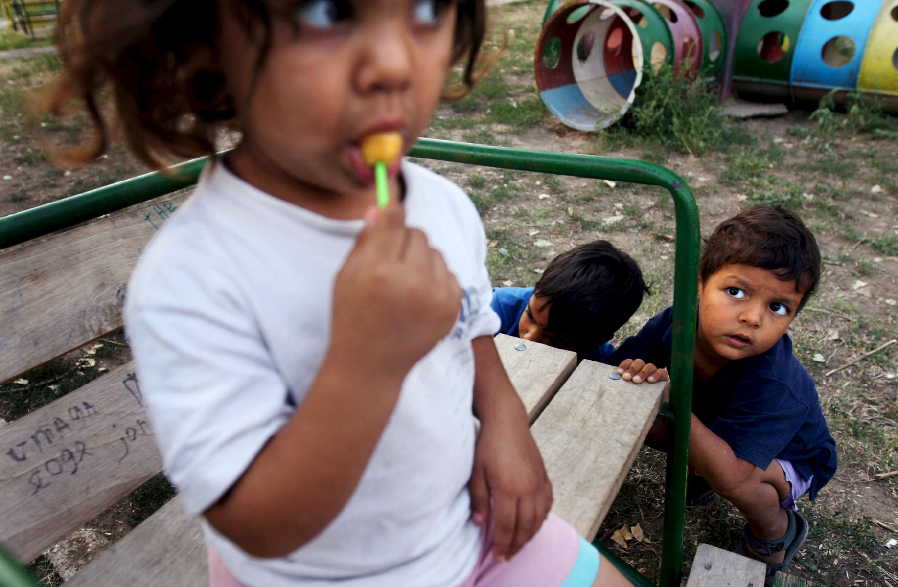 A little girl sucks a lollipop under the hungry gaze of a little friend at the Dom Maika i Dete (Home for Mother and Child) adoption home in Vidin, Bulgaria on August 31, 2008.Children for adoption in Vidin, Bulgaria, live here. The home's director, Maria Rangelova, describes that two decades ago, the home carried more than double the children, who were mostly given away because they were born out of wedlock. While the number of children has decreasted from about 180 to 80 from waning birth rates and shifting cultural perceptions of birth outside of marriage, there remain many kids in need of adoption. Now, she says, most parents who give their children away do so because of financial want -- one that robs them of the ability to support their kids, or leaves them unable to cure an illness that has incapacitated them as caregivers. The home often struggles to provide an adequate amount of toys, snacks and personnel necessary for the children's caregiving.