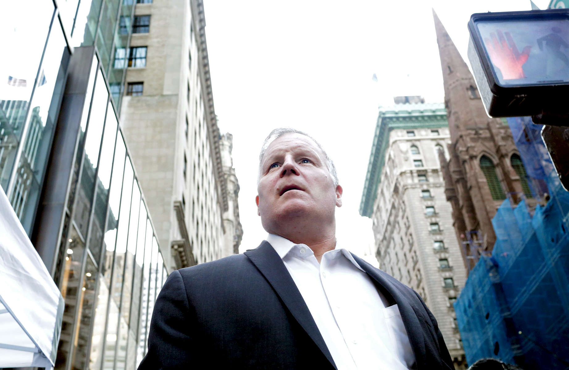 "A man stares up at Trump Tower, the current residence of Republican President elect Donald Trump, in Manhattan, NY on November 28, 2016.-""Trump Gawkers{quote} is a visceral look at what draws people to Trump Tower, the current residence of U.S. President elect Donald Trump. Hoards of people undertake the trek, bearing security and weather roadblocks, to stare, gawk, absorb, record. The magnetism to the tower (and by extension, to the man inside it,) manifests in the sheer numbers of daily visitors, as well as in the fascination etched across their faces. Upon first look, the time so many spend there seems like sport and amusement, but underneath upturned eyes and selfie smiles prevails an undercurrent of anxiety - and not just for those who didn't want Trump in the Oval Office. Some of the electorate that voted against Hillary is now unsure for which version of Trump they voted. People's upward gazes, no matter their political views, seek answers: How could this happen? Or now that it has, what will it mean?"