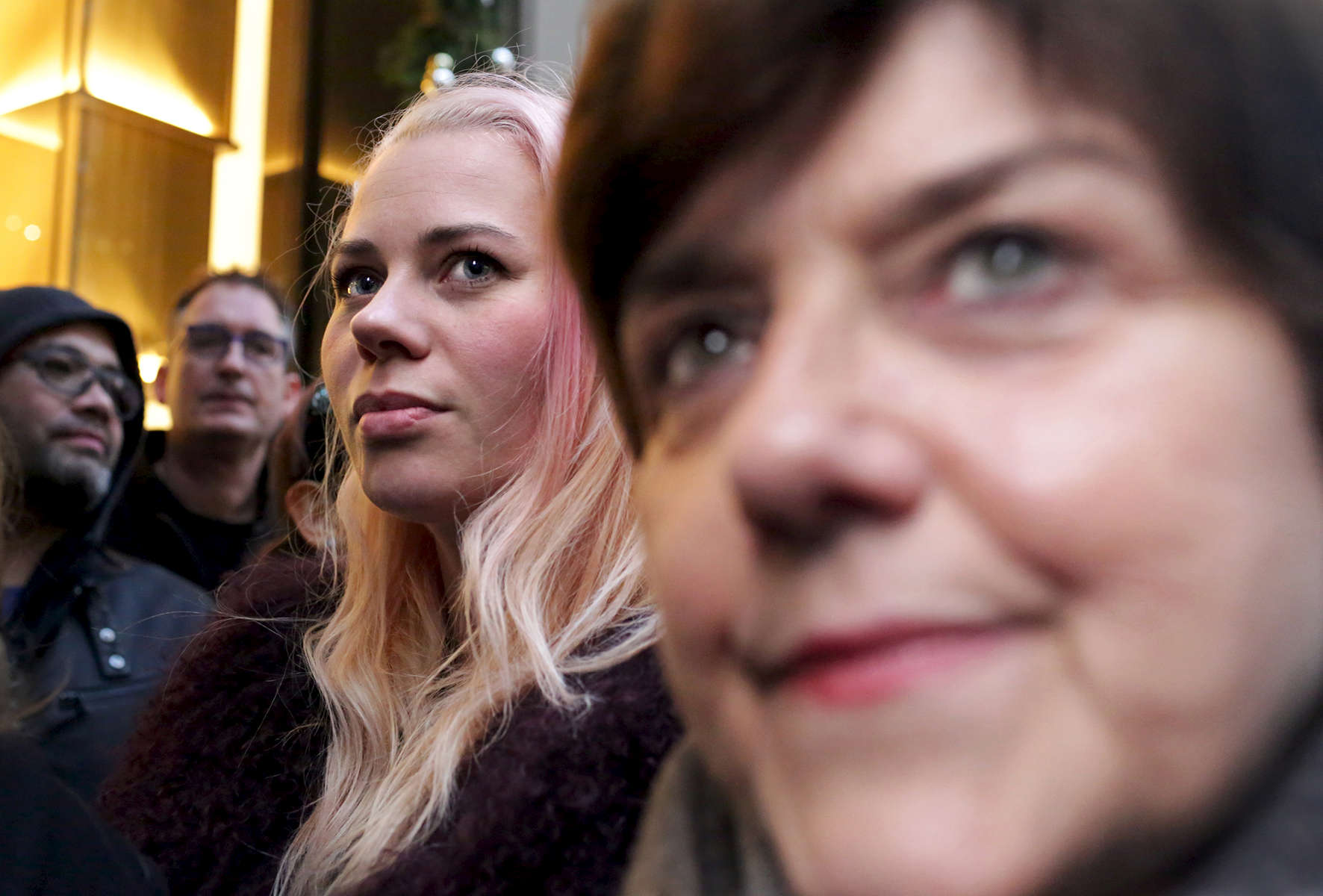 """Passersby walk through a throng of people photographing Trump Tower, the current residence of Republican President elect Donald Trump, in Manhattan, NY on November 22, 2016.-""""Trump Gawkers{quote} is a visceral look at what draws people to Trump Tower, the current residence of U.S. President elect Donald Trump. Hoards of people undertake the trek, bearing security and weather roadblocks, to stare, gawk, absorb, record. The magnetism to the tower (and by extension, to the man inside it,) manifests in the sheer numbers of daily visitors, as well as in the fascination etched across their faces. Upon first look, the time so many spend there seems like sport and amusement, but underneath upturned eyes and selfie smiles prevails an undercurrent of anxiety - and not just for those who didn't want Trump in the Oval Office. Some of the electorate that voted against Hillary is now unsure for which version of Trump they voted. People's upward gazes, no matter their political views, seek answers: How could this happen? Or now that it has, what will it mean?"""