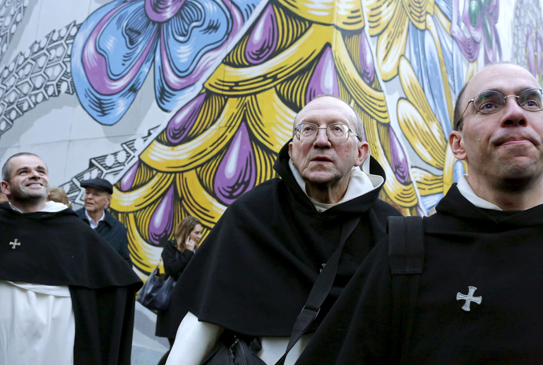 (L-R) Fr. Ambroise Pellaumail, Fr. Louis De Blignieres, and Fr. Reginald Rivoire, from Fraternite Saint Vincent Ferrier in France, walk by Trump Tower, the current residence of Republican President elect Donald Trump, in Manhattan, NY on November 18, 2016.-{quote}Trump Gawkers{quote} is a visceral look at what draws people to Trump Tower, through in-depth interviews and still photos - a project I started the day after the election. At first, I simply followed where my assignments sent me, but then found myself returning to the place on my own, unable to look away - and I wasn't alone. Hoards of people undertake the trek, bearing security and weather roadblocks, to stare, gawk, absorb, record. The magnetism to Trump Tower (and by extension, to the man in the tower,) manifests in the sheer numbers of daily visitors, as well as in the fascination etched across their faces. Upon first look, the time so many spend there seems like sport and amusement, but underneath upturned eyes and selfie smiles prevails an undercurrent of anxiety - and not just for those who didn't want Trump in the Oval Office. Some of the electorate that voted against Hillary is now unsure for which version of Trump they voted. People's upward gazes, no matter their political views, seek answers: How could this happen? Or now that it has, what will it mean?