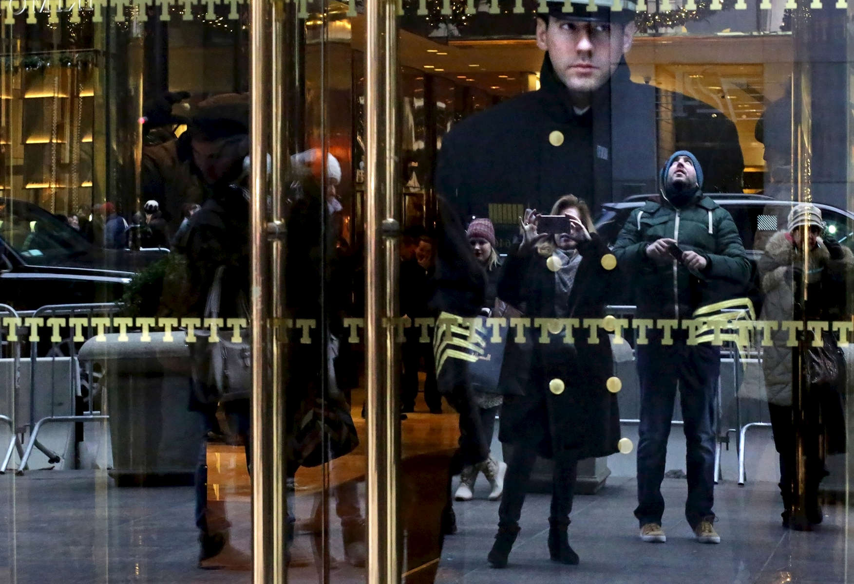 David Skellington,  doorman of Trump Tower of eight years, the current residence of Republican President elect Donald Trump, looks out onto passersby photographing the building in New York, NY on December 15, 2016. On crowds constantly recording Trump Tower, Skellington said: {quote}It's interesting, you see a lot of people, it's history. But this could be awkward, so many people taking pictures. I'd rather be behind the camera. My family and friends are always seeing me on the news. Tourists say, 'you're famous.' {quote} -{quote}Trump Gawkers{quote} is a visceral look at what draws people to Trump Tower, through in-depth interviews and still photos - a project I started the day after the election. At first, I simply followed where my assignments sent me, but then found myself returning to the place on my own, unable to look away - and I wasn't alone. Hoards of people undertake the trek, bearing security and weather roadblocks, to stare, gawk, absorb, record. The magnetism to Trump Tower (and by extension, to the man in the tower,) manifests in the sheer numbers of daily visitors, as well as in the fascination etched across their faces. Upon first look, the time so many spend there seems like sport and amusement, but underneath upturned eyes and selfie smiles prevails an undercurrent of anxiety - and not just for those who didn't want Trump in the Oval Office. Some of the electorate that voted against Hillary is now unsure for which version of Trump they voted. People's upward gazes, no matter their political views, seek answers: How could this happen? Or now that it has, what will it mean?