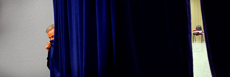 (L-R) Actor John Voight peeks out behind the curtains, from which U.S. Presidential hopeful Rudy Giuliani (R-NY) is about to enter a rally with him and former FBI director Louis J. Freeh at the Fantasy of Flight museum in Polk City, Florida, on Sunday, January 20, 2008; and an American flag sits folded on a chair backstage as U.S. Presidential hopeful Sen. Hillary Clinton (D-NY) speaks at the Bluegrass Cafe in Tama, Iowa, on Nov. 19, 2007. (For The New York Times)