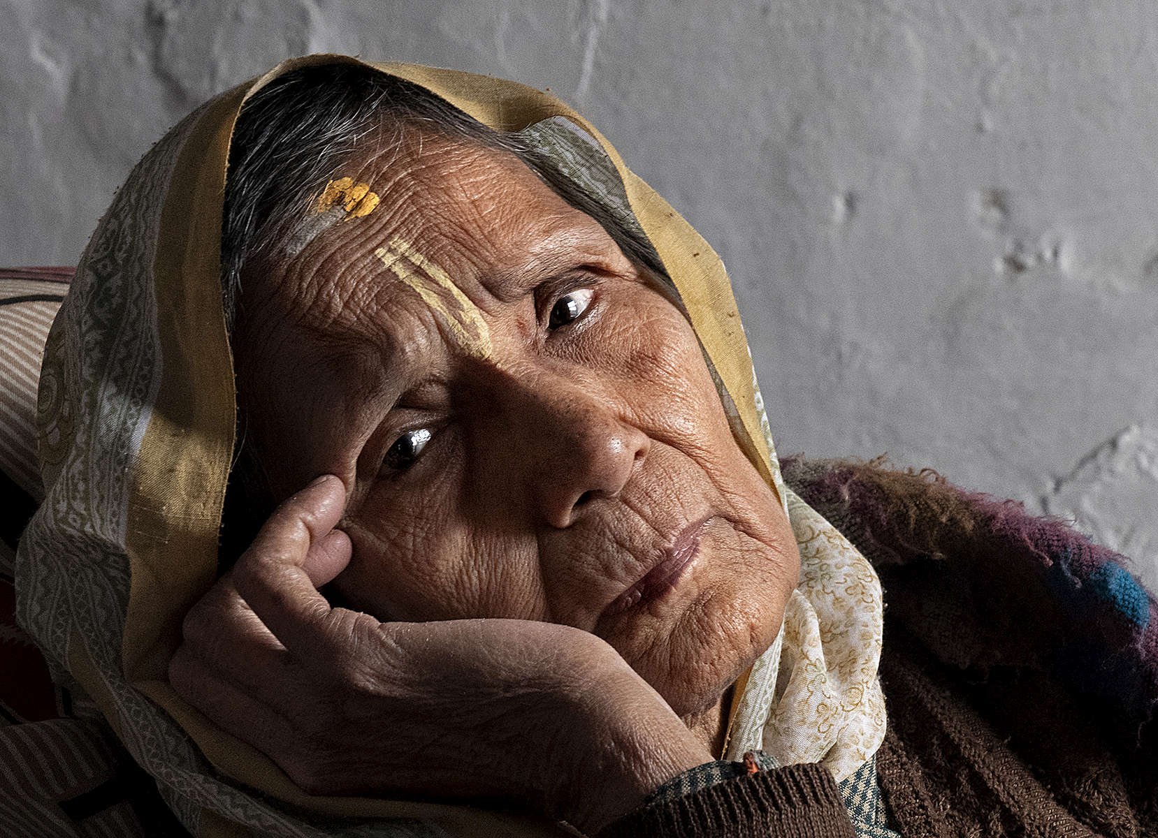 Meena Devi, 78, a widow, falls deep in thought at Rak Kuti ashram in Varanasi, India on January 07, 2019. Meena is originally from Nepal, and has lived in the ashram for the past 25 years. Before that, she lived in the same building as Sita Devi, 52, and her mother-in-law, Goma Devi, 96, who now also occupy this ashram. Meena is a child widow. {quote}Maybe I was cursed and I would have been forbidden to attend any functions because my husband died at a young age,{quote} she says. So with the help of relatives she moved here to live among other widows. She didn't want to marry again after her husband's death.