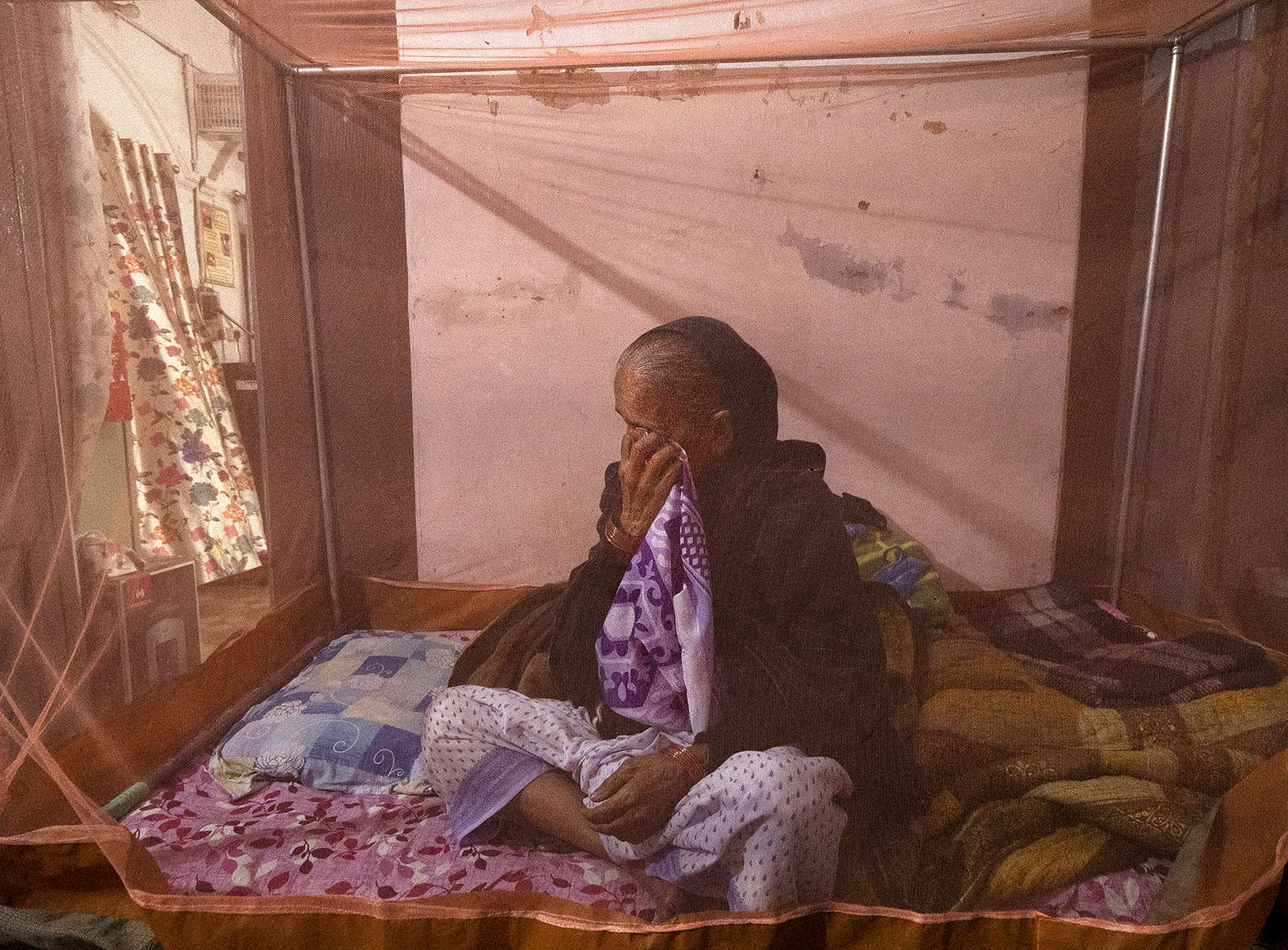 Munni Devi, who estimates she is 90 years old, sitting behind the mosquito net of her bed becomes emotional while talking about her life, at Durga Kund Help Line ashram in Varanasi, India on January 08, 2019. Munni says she doesn't remember the age of her husband - he was a few older than her. A mother of two, one of her sons was kidnapped at the age of 12 and the other son died in an accident. {quote}I worked so hard to educate him hoping that one day he will become an engineer and take care of me. But God had other plans. I have no one, I can't cry to anyone,{quote} she says, adding that she was left out on the streets following her husband's death, as her landlord sold her rented home. {quote}Now I have been here for some time, thinking about why God did this to me and passing my time.{quote}