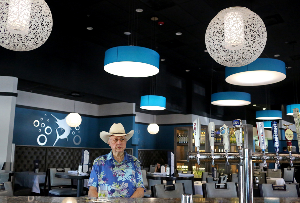 Paul Bukovski, 78, has a drink at Bluefin Grill & Bar amidst coronavirus-related event cancellations at Brownwood Paddock Square in The Villages, Florida, U.S., ahead of the upcoming Democratic primary March 15, 2020.  REUTERS/Yana Paskova
