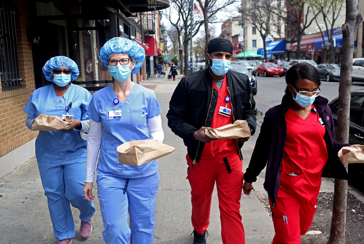 (L-R) Marie Belkacemi, Starla Sims, Melvin White, and Shana Thomas, registered nurses working in the emergency department of St. Barnabas Hospital in the Bronx, NY, carry their lunches on Arthur Ave. on April 10, 2020. (Photo by Yana Paskova/For The Washington Post)
