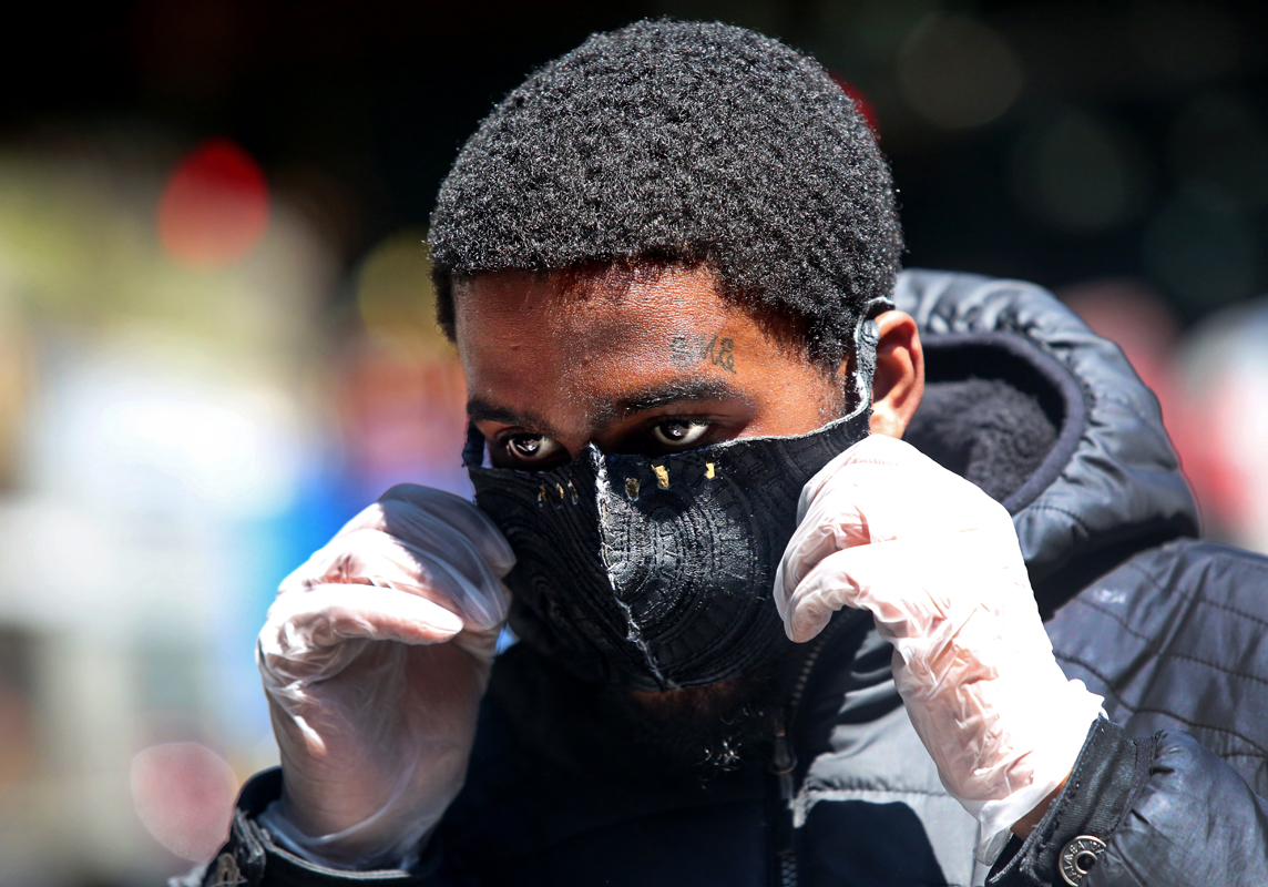 R&B singer Robert Huggins, 19, adjusts his mask after buying gloves from a woman with a face shield under the elevated stop of the 4 train at E. Burnside Ave. and Jerome Ave. in the Bronx, NY, on April 19, 2020. (Photo by Yana Paskova/For The Washington Post)