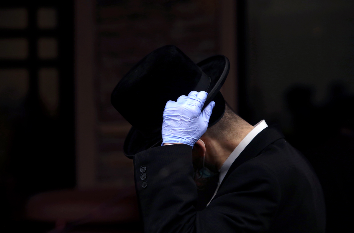 A man adjusts his hat as he waits in line to get tested for coronavirus antibodies at the Refuah Health Center on April 24, 2020 in Spring Valley, NY. (Photo by Yana Paskova/Getty Images)
