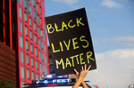 A protester holds up a Black Lives Matter sign in front of a cop car by the Barclays Center in Brooklyn, NY on June 06, 2020.