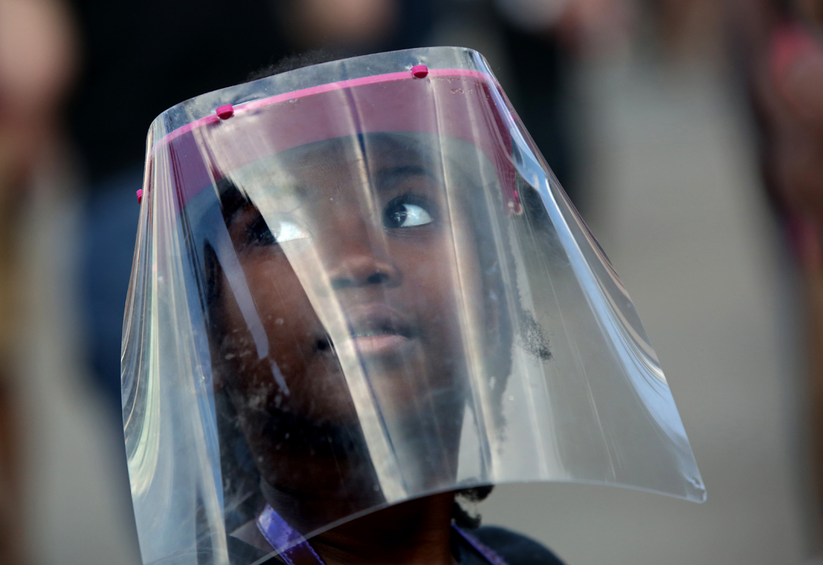 A young girl under a face shield (who wanted to be photographed, with her mother's permission,) watches hundreds of people gather to protest police violence at Grand Army Plaza in Brooklyn, New York, on June 07, 2020. Peaceful demonstrations, which elicited teargassing, rubber bullets and mass arrests by police, spread throughout the country and the world in response to the death of George Floyd, an African-American man who Minneapolis police killed via extensive neck and back compression during an arrest at the end of May. Photo by: Yana Paskova © 2020