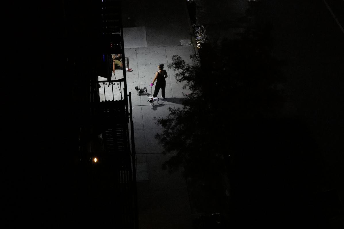 A woman walks her dog on an emptied, darkened Brooklyn street on August 26, 2020.