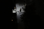 A woman walks her dog on an emptied, darkened Brooklyn street on August 26, 2020.
