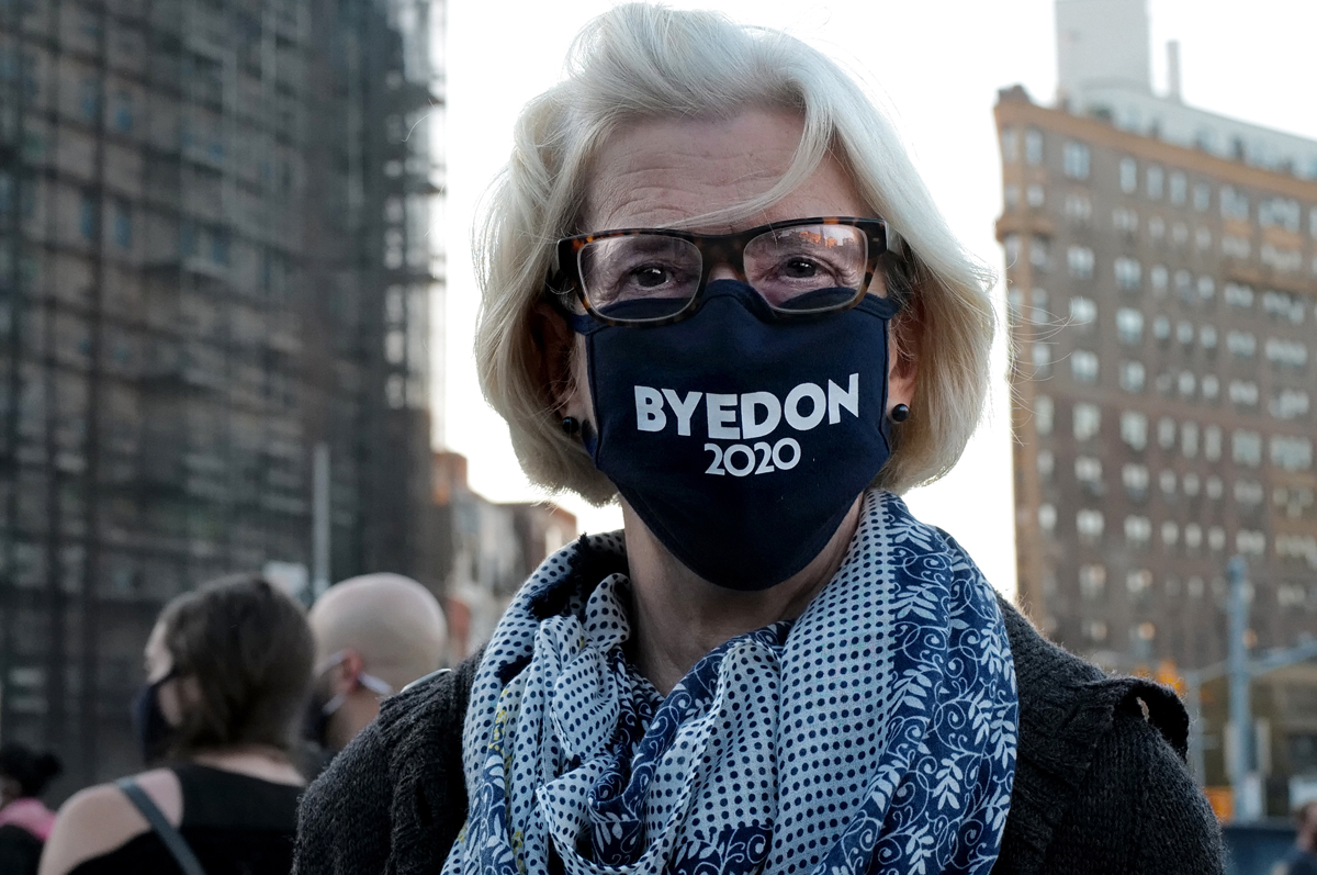 A woman joins masses of people in the streets to celebrate after Democratic candidate and former vice president Joe Biden is projected to be the next president of the United States, defeating his controversial Republican rival, Donald Trump, on November 07, 2020 at Grand Army Plaza in Brooklyn, New York.