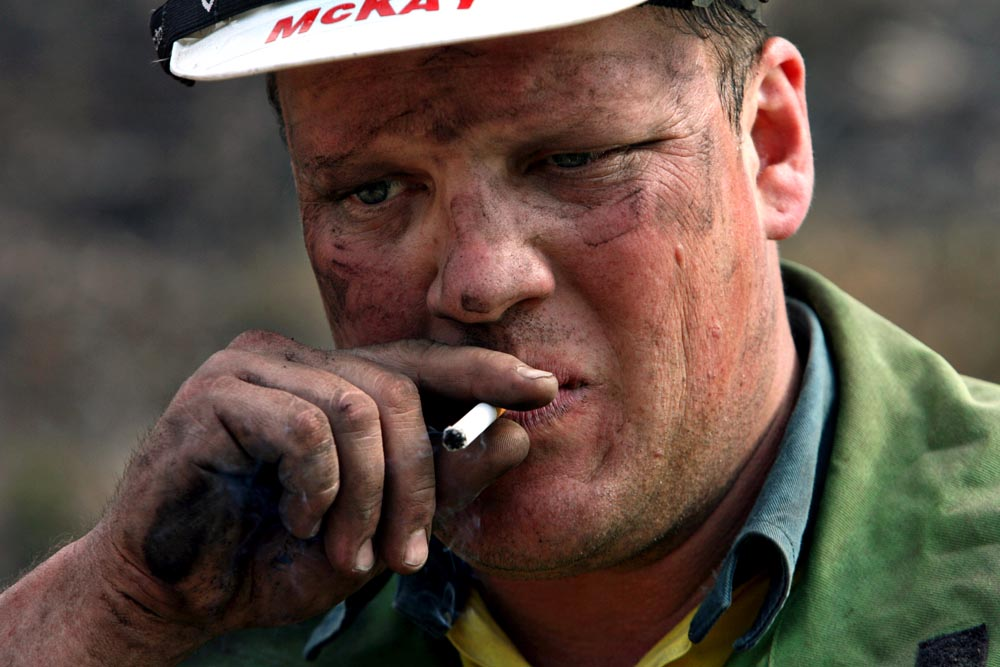 Brendan McKay, a firefighter with DSE, stops to smoke a cigarette before continuing his efforts to help mop up a fire.