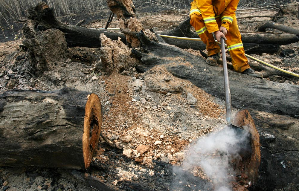 First year CFA firefighter Ash Lewis uses a rakehoe to mop up the remains of a bushfire near Jamieson. The bushfire, part of the Great Divide North fire, had been burning for more than two weeks in large expanses of northern Victoria.