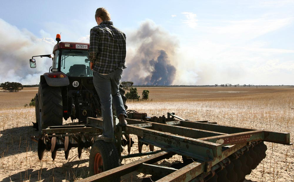 Ninth grader Matthew Wallis stands on his uncle's tractor as he watches smoke billow out from a bushfire at the Little Desert National Park. Matthew and his uncle Trev Wallis waited nervously for hours to see if the fire was going to spread from the park into his family's farm land. {quote}It could take six hours or ten minutes to head out into the paddock. You just don't know,{quote} Trev Wallis said.