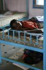 Arunkumar takes a Saturday afternoon nap on his bunk bed, while another child sleeps on the floor due to the lack of beds.