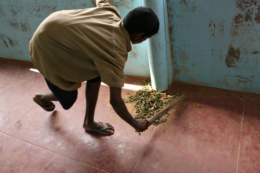 Samkuttia, who is intellectually disabled and was found working as a ragpicker when he was 9, sweeps the hallway during the daily cleanup.