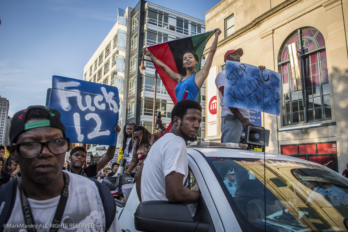 Demonstrators ride on and march alongside  a truck leading the Black Lives Matter march in Philadelphia. Trucks led the procession up Broad Street for four miles to FDR Park across from the Wells Fargo arena, site of the DNC.