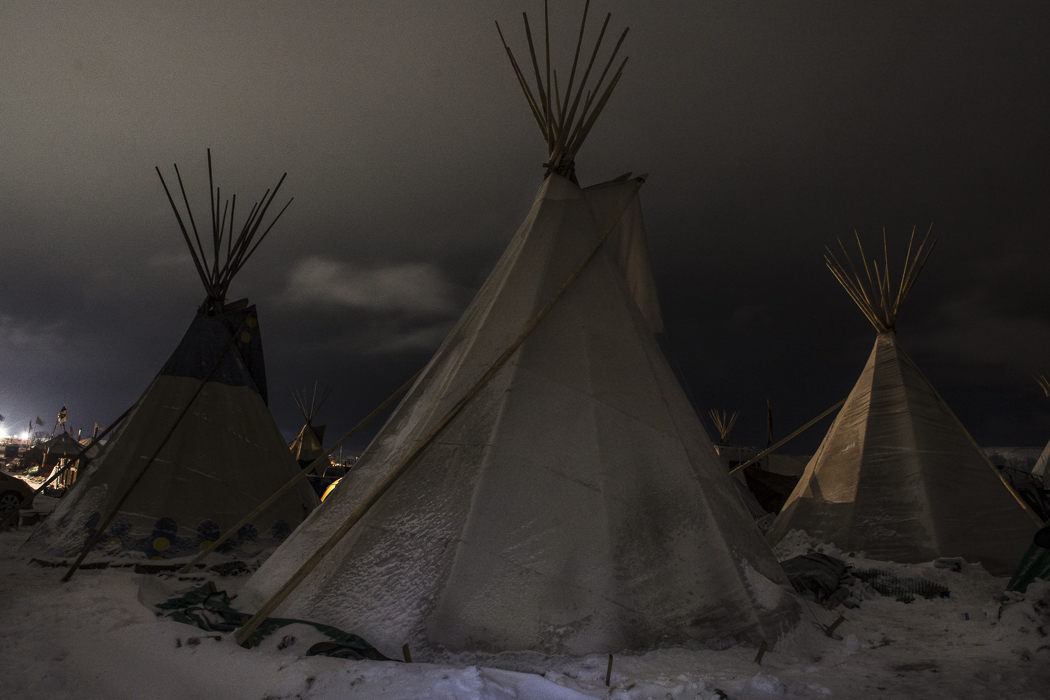 Teepees illuminated by the floodlights of the ongoing DAPL pipeline construction in the background.