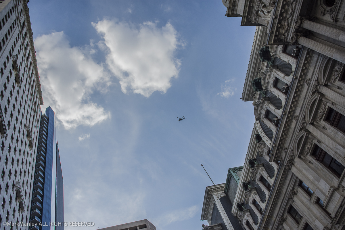 A police helicopter circles over a demonstration below on the south side of City Hall in Philadelphia during the DNC.