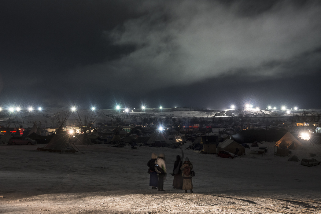 A group of women atop {quote}Facebook Hill{quote} at the Oceti Sakowin camp peer out towards the lights from the DAPL pipeline construction.