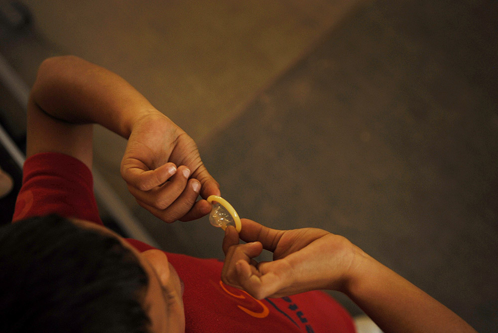 A young Gente Joven peer promoter demonstrates correct handling of a condom during a sexual and reproductive health presentation in a rural school outside of San Juan Rio, Mexico.
