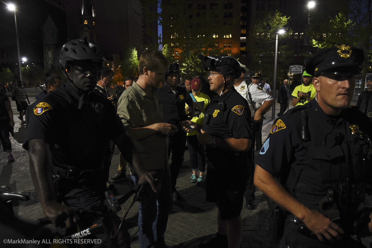 A Cleveland police bike patrol detains and checks the I.D. of a man near Settlers Landing during the RNC. Police presence  was large, with 2,800 additional officers brought in from around the country to supplement the Cleveland Department. Despite the large numbers, Cleveland Police reported only 24 total arrests related to the RNC.