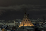 A teepee stands illuminated amidst the parked cars.