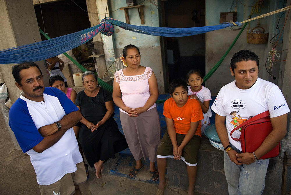 Umberto (far right), Mexfam youth promoter coordinator, meets with a promoter's family at their home.Working closely with the parents and families of the young promoters has been key in building support and acceptance of the program in the larger community.