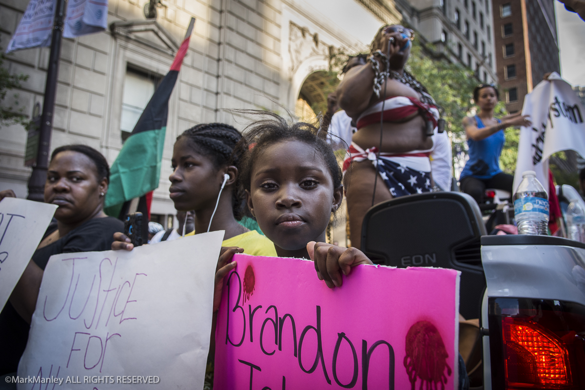A young girl looks back at the photographer from the back of a truck leading the Black Lives Matter march in Philadelphia, site of the 2016 DNC.