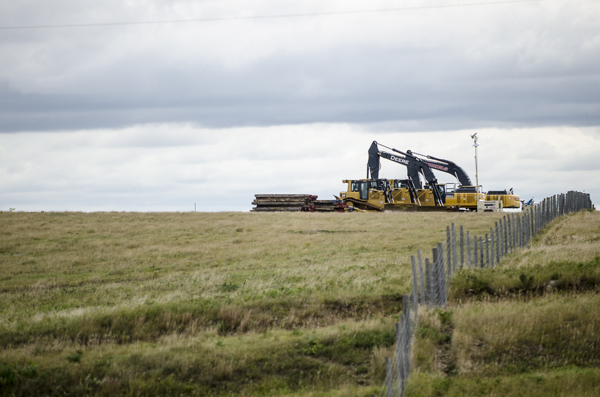 Heavy Equitment used by Energy Transfer Partners in the construction of the Dakota Access Pipeline stand idle as marchers pass by on a prayer walk to the site of a prior confrontation between protesters and private security hired by Energy Transfer Partners .
