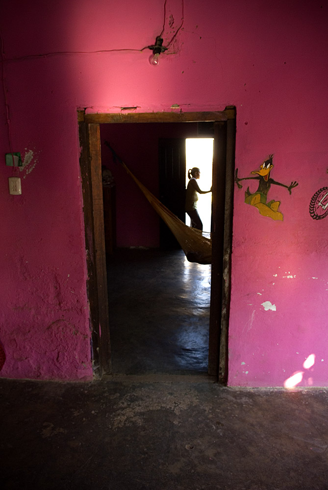 A young girl looks out her doorway onto the street in Santa Maria, Xhadani, Mexico. Mexican population studies compiled in1995 and 2006 estimate that around 20% of single, young adolescents aged 15-19 have initiated sexual activity with almost no use of contraception (Mendoza, 2006).