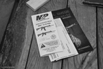 Printed safety materials lay on a picnic table next to the weapons check-in area. All weapons were inspected and zip-tied prior to being allowed to enter the church.