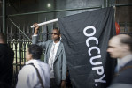 A man holds an Occupy banner aloft on lower Broadway near Wall Street on the morning of September 17th, the first year anniversaryof the Occupy Wall Street movement.